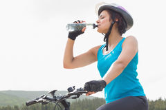 Athletic woman on mountain bike drinking water Stock Image