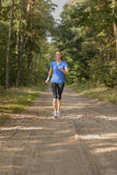 Athletic woman out jogging in a forest Stock Photography