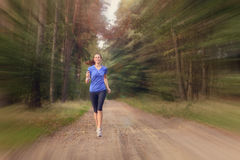 Athletic woman out jogging in a forest Stock Image