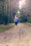 Athletic woman out jogging in a forest Royalty Free Stock Images