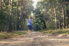 Athletic woman out jogging in a forest Stock Photo