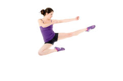Athletic woman performing a flying side kick Royalty Free Stock Images