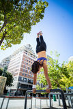 Athletic woman performing handstand on bar Royalty Free Stock Photos