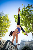 Athletic woman performing handstand on bar Stock Photo