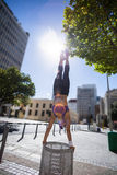 Athletic woman performing handstand on bin Royalty Free Stock Images