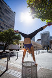 Athletic woman performing handstand and doing split on bin Stock Photography