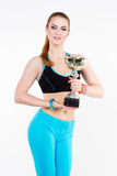 Athletic woman poses with the championship trophy Royalty Free Stock Photo