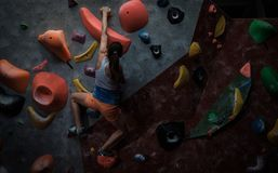 Athletic woman practicing in a bouldering gym. Athletic woman practising in a bouldering gym royalty free stock photo