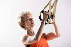 Athletic woman pulling fitness cords Stock Photos