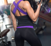 Athletic woman pumping up muscles with dumbbells Stock Images