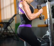 Athletic woman pumping up muscles with dumbbells Stock Photos