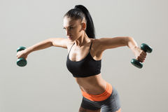 Athletic woman pumping up muscles with dumbbells Royalty Free Stock Image