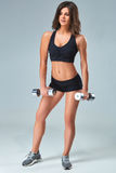 Athletic woman pumping up muscles with dumbbells on gray background Stock Image