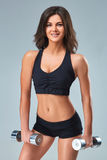 Athletic woman pumping up muscles with dumbbells on gray background Stock Images