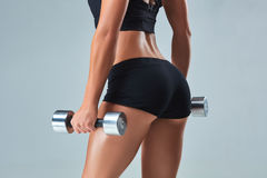 Athletic woman pumping up muscles with dumbbells on gray background. Beautiful woman with a sports figure stands with her back to the camera Stock Images