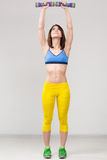 Athletic woman pumping up muscles with dumbbells Royalty Free Stock Images