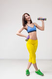 Athletic woman pumping up muscles with dumbbells Stock Photo