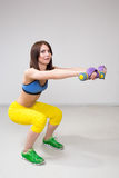 Athletic woman pumping up muscles with dumbbells Royalty Free Stock Photos