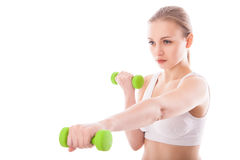Athletic woman pumping up muscles with dumbbells Royalty Free Stock Photography