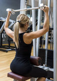 Athletic woman pumping up muscles Royalty Free Stock Photo