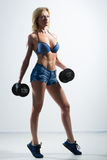 Athletic woman pumping up muscules with dumbbells Royalty Free Stock Photo