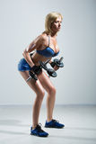 Athletic woman pumping up muscules with dumbbells Royalty Free Stock Photos