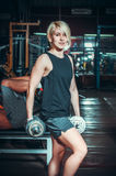 Athletic woman pumping up muscules with dumbbells Stock Photos