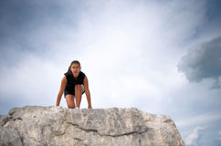 Athletic woman ready. Athletic woman on a rock starting to run Royalty Free Stock Image