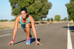 Athletic woman ready for sprint running. Athletic woman running in countryside road. Fitness female runner in ready start line pose outdoors in summer sprint Stock Photo
