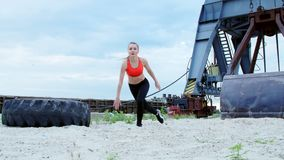 Athletic woman in a red top and black leggings performs different strength exercises using a large heavy tractor wheel stock footage
