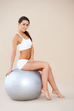 Athletic woman relaxing on fitness ball Royalty Free Stock Images