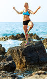 Athletic woman relaxing - practicing yoga on the rocks by the se Royalty Free Stock Photos