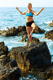 Athletic woman relaxing - practicing yoga on the rocks by the se Stock Photo