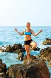 Athletic woman relaxing - practicing yoga on the rocks by the se Royalty Free Stock Images