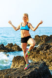 Athletic woman relaxing - practicing yoga on the rocks by the se Stock Images