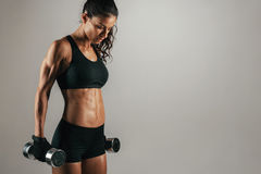 Athletic woman resting with weights at her sides Royalty Free Stock Images