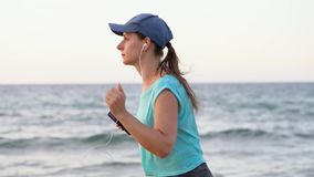 Athletic woman running along the beach. Video at different speeds - quick, normal and slow stock video footage