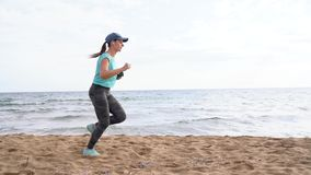 Athletic woman running along the beach. Video at different speeds - quick, normal and slow stock footage