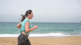 Athletic woman running along the beach stock video