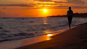Athletic woman running along the beach at sunset stock footage