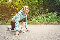 Athletic woman running in countryside road. Fitness female runner in ready start line pose outdoors in summer sprint. Challenge stock image