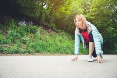 Athletic woman running in countryside road. Fitness female runner in ready start line pose outdoors in summer sprint. Challenge stock photos
