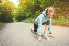 Athletic woman running in countryside road. Fitness female runner in ready start line pose outdoors in summer sprint. Challenge stock photography