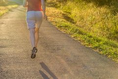 Athletic woman running at countryside trail in sunrise light. stock photography