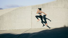 Athletic woman running and jumping outdoors. Muscular female exercising in morning Royalty Free Stock Photo