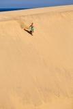 Athletic woman running on sand desert dunes Stock Photos