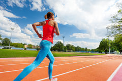 Athletic woman running on stadiums track in summer Stock Photo