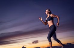 Athletic woman running at sunset dusk Royalty Free Stock Photography