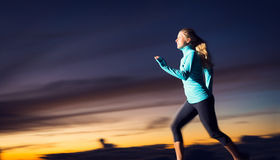 Athletic woman running at sunset dusk Stock Image