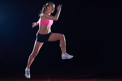 Athletic woman running on track Stock Photography